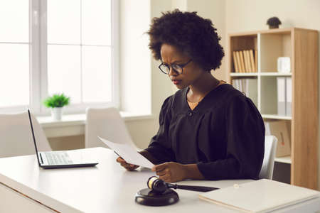 Frowning young african american female judge reading paper document sitting at desk front of laptop in courtroom. Legal trial or tribunal, paperwork and criminal data or jury order investigation Stock fotó