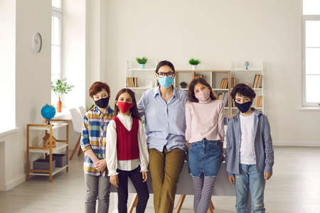 Young female teacher and pupils group wearing medical face mask standing together looking at camera portrait. Classroom interior. New normal school education to prevent covid-19 coronavirus spreading