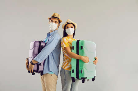 Vacation in pandemic condition, new travel rules. Happy family couple wearing protective respiratory facial mask holding luggage bag looking at camera standing over studio copy space background