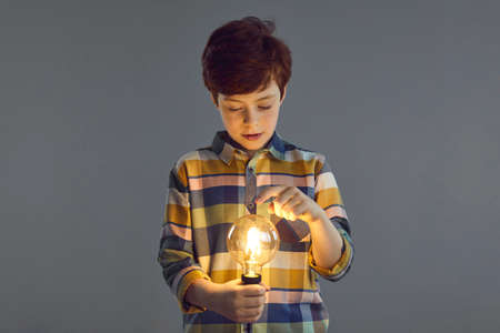 Curiosity, cognition and innovative knowledge concept. Inquisitive confident handsome caucasian preteen boy touching glowing lightbulb lamp in hand with interest standing isolated on studio background