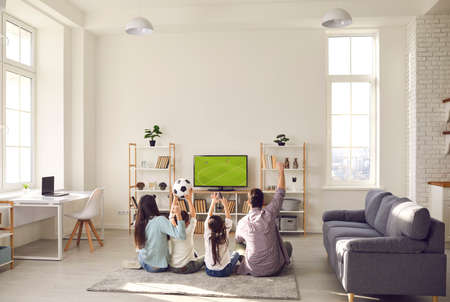 Football match, leisure and happy family sport fan pastime together. Excited parent with overjoyed children watching soccer game on tv sitting on floor carpet in living room at home. Rear view