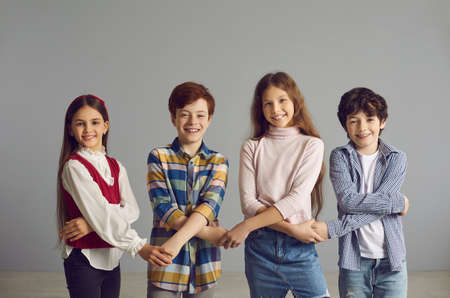 Portrait of a smiling group of children standing against the gray wall and holding hands. Concept of socialization, interaction, cooperation and relationships with peers.