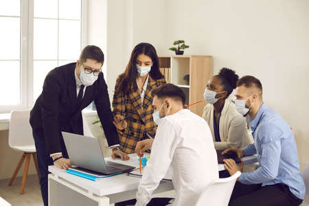Multiracial team all in face masks working on business project in office meeting. Multiethnic people trying to keep safety measures and take precautions