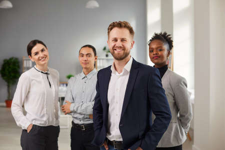 Successful international team, business development, Teamwork concept. Group of young smiling confident mixed race workers standing and looking at camera together in office