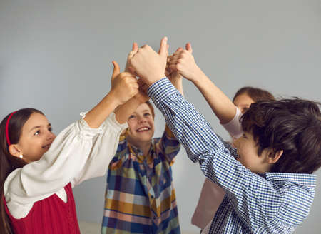 Team of happy children give thumbs up as they join hands together. Group of preteen volunteers doing like okay gesture. Little kids feeling confident and empowered. Bunch of best friends having fun