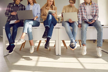 Cropped image of students sitting on the desks with modern gadgets and preparing for lectures. Concept of learning, work, digital technology and modern gadgets for the learning process.