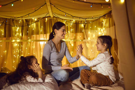 Family leisure time, motherhood and childhood concept. Happy loving mother playing with two adorable daughters in home tent decorated night lights lamp in evening before bedtime