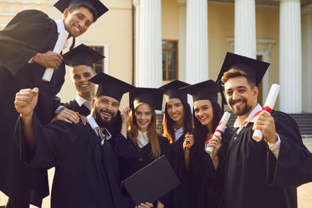 Group portrait of happy graduates near their alma mater. Smiling university students in traditional academic gowns and caps holding diplomas looking at camera after graduation ceremony