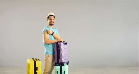 Caucasian millennial man traveler standing with luggage suitcase show arm with patch. Studio portrait on grey copy space