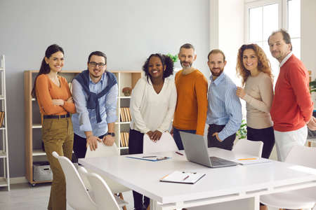 Diverse dream team reaching success together. Group portrait of happy business people, colleagues and teammates looking at camera and smiling standing at office table after corporate work meeting