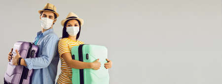 Couple going on holiday trip together. Man and woman in face masks holding suitcases standing isolated on light gray text copyspace background.