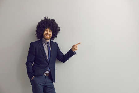 Adult successful caucasian bearded hipster business man in funny afro curly hair wig loudly laughing pointing with index finger to something at right on studio copy space. Advertisement concept