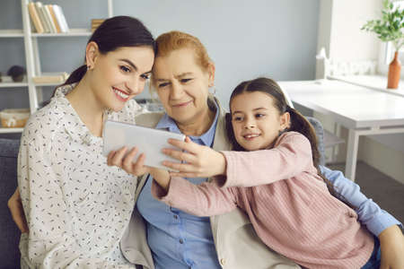 Happy family moments. Little girl taking a selfie with her mother and grandmother. Child with a phone in his hands makes a family portrait depicting three generations. Family and relations concept.