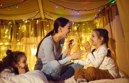 Happy family spend fun time together at home lifestyle. Overjoyed mother playing with adorable children in tent with glowing garlands light decoration at evening. Cheerful kids and loving mom