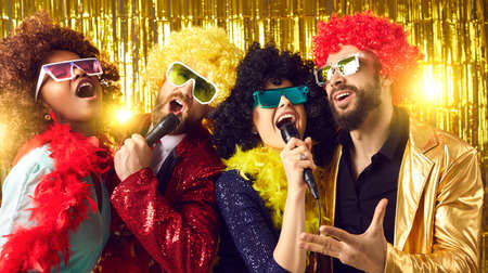 Male and female music show band with mikes performing on golden stage. Happy people dressed in funny fancy costumes having fun singing at New Year, Christmas, birthday or Halloween karaoke disco party