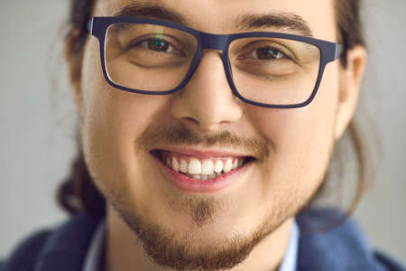 People emotion studio shot. Smart handsome bearded young asian man in eyeglasses with smiling expression face portrait close up with blurred background and focus on white toothy smile