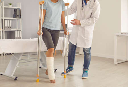 Orthopaedic recovery. Cropped image doctor supports a patient with a broken leg while walking on crutches in a hospital office. Concept of treatment of serious physical injuries.