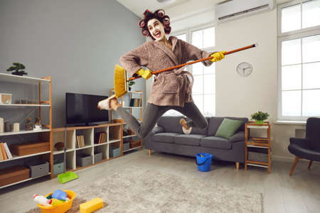 Funny positive housewife cleaning her house, fooling around and having fun. Happy energetic woman in hair curlers tidying up home, jumping up in air, singing songs and playing on pretend mop guitar Reklamní fotografie