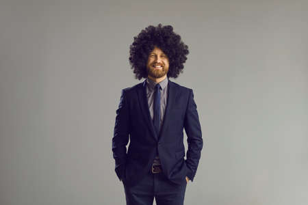 Portrait of friendly guy with crazy hair style. Happy young man in elegant dark blue business suit and funny thick curly wig smiling at camera standing hands in pockets on gray studio background