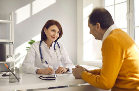 Health care for senior citizens. Happy smiling young woman who works as doctor sitting at desk in office and looking at patient. Mature man seeing friendly physician or general practitioner at clinic