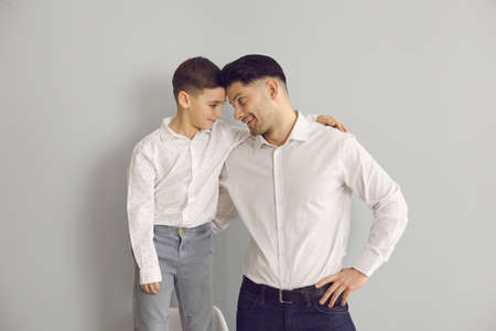Happy kid and dad having fun together. Young father and son in white dress shirts looking at each other. Little child and his daddy standing in studio with light gray background Reklamní fotografie