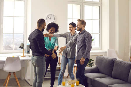 Male and female friends welcoming young guy at cozy party at home. Group of happy people excited to meet and hug coworker. Congratulations on promotion, warm reunion, enjoying good time together