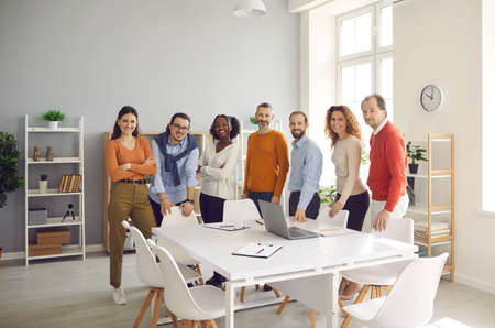 Dream team reaching success together. Group portrait of happy smiling confident diverse business people, colleagues and teammates looking at camera standing at table after corporate office meeting