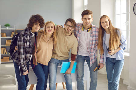 Group of happy smiling young people in casual clothes standing in modern classroom after a lesson. Portrait of five friendly high school, college or university students looking at camera all together Stock Photo