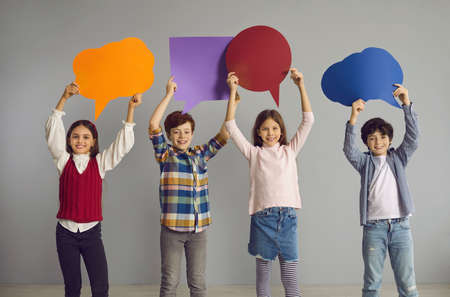 New generation voicing out opinions. Team of happy school children showing colorful speech balloon paper cards. Smiling little kids holding empty thought bubble placards standing together in studio