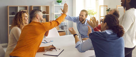 Happy successful multiracial business team clapping hands while two colleagues giving high fives gesture each other. Businesspeople laugh and cheer sitting at table in office on briefing meeting