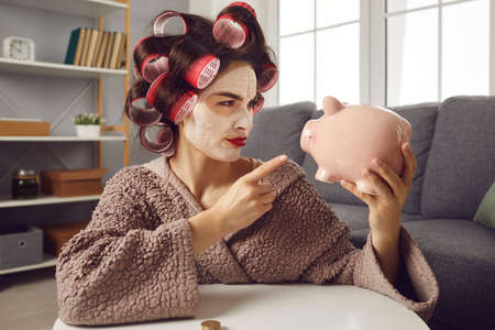 Challenge accepted. Saving up can be difficult, but Im determined this time. Funny young lady in hair curlers wagging finger at piggy bank. Setting financial goal and planning future expenses concept