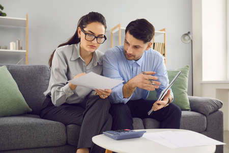 Family budget planning. Married couple analyzes and calculates their financial accounts while sitting on the couch. Family plans expenses and purchases or calculates payment for utilities and rent.