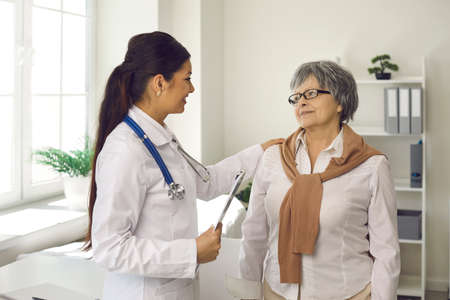 Medicine and healthcare for elderly patient. Senior woman at professional doctor appointment in modern clinic. Caucasian female specialist putting hand on aged lady shoulder telling good news