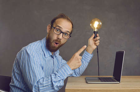 Portrait of funny surprised nerdy bearded man in geek eyeglasses sitting at office desk with laptop computer, looking at camera and showing bright lightbulb hes holding in hand. Amazing idea concept