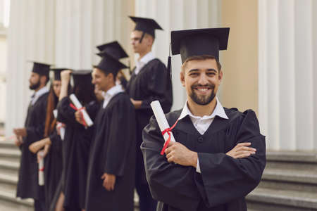 Happy confident man in graduation gowns holding diploma and smiling while his friends standing in the background. Graduation from the university. Education, university and college concept. 版權商用圖片