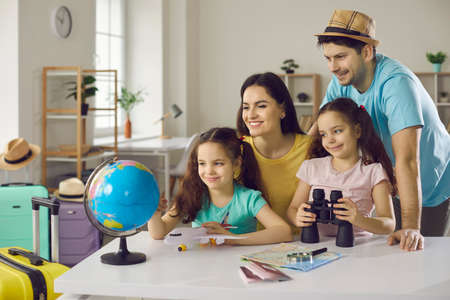 Travel planning. Cheerful and active family smiling and looking at the globe in preparation for a new vacation trip. Concept of active recreation, summer vacations and travel around the world. 版權商用圖片