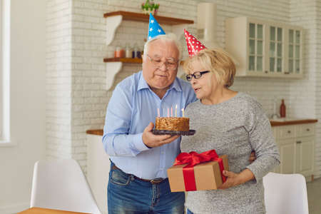 Quiet birthday celebration at home. Happy mature couple in cone-shaped hats blowing out candles together on a cake. Older man tenderly greeted his wife with a special date.