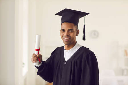Portrait of happy young African-American man in black graduation robe and hat holding diploma scroll and smiling at camera. Headshot of college or university male student with his graduate certificate 版權商用圖片