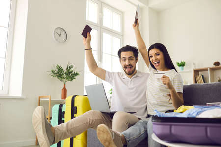 Ready for vacation. Happy young couple in love having fun on couch at home glad theyve packed travel bags, picked airline online and bought tickets that soon will get them to trip destination abroad