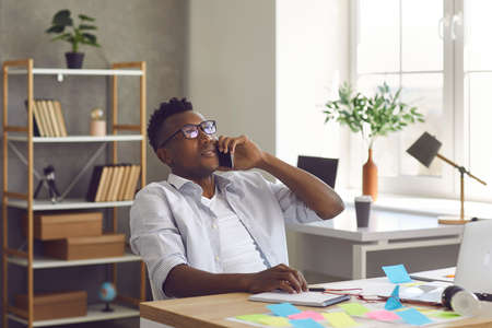 Young Afro American man talking on mobile. Black businessman making a phone call. Successful relaxed entrepreneur sitting at office desk, leaning back on chair and talking to colleague on smartphone