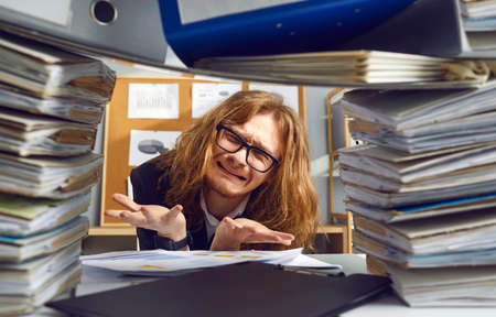 Miserable stressed helpless insane long haired accountant guy in glasses crying unable to do crazy paperwork workload, sitting at messy office table with lots of huge binders, folders, paper documents