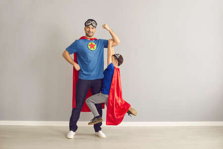 Happy strong young dad and active little child dressed as superheroes having fun at home. Father and son in red super hero capes playing together in studio. Family relationship, power concept