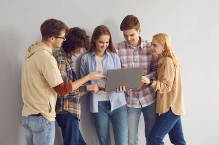 Happy teen girl showing off new laptop to smiling cheerful casual teenager friends group standing over studio grey copy space background. Portrait of young people, communication and technology 版權商用圖片