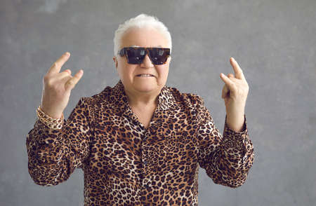 Steep mature man shows a rock sign with both hands standing on a gray background. Stylish gray-haired man in sunglasses, a shirt with a leopard print and a gold bracelet on his arm poses in the studio