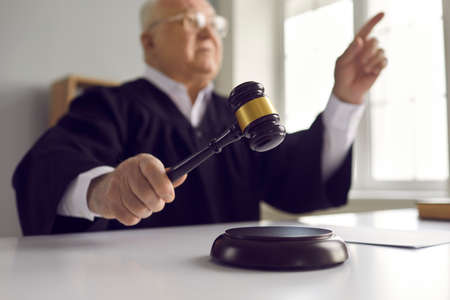 Senior man of law pronounces sentence in court. Mature judge finds the accused guilty, passes fair judgement and rules the case closed. Close-up of hand holding wooden gavel and hitting sound block