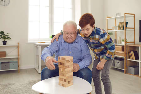 Senior man enjoying board games while spending time with his grandson at home. Supportive little child teaches grandfather to play jenga and gives advice on how to carefully remove wooden blocks Фото со стока