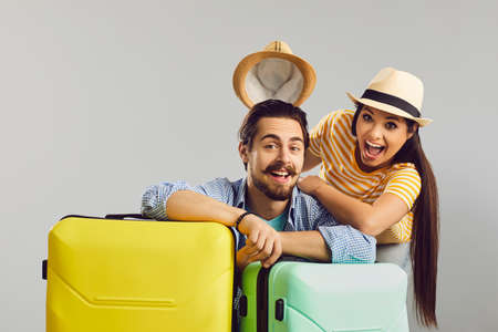 Cheerful wife takes off husband hat and laughing. Happy overjoyed funny Caucasian family couple traveler with luggage bag ready for summer travel holiday vacation studio headshot portrait