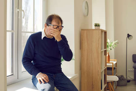 Desperate senior man crying sitting alone on windowsill, trying to overcome grief or accept bad news. Older adult weeping stressing out over life problems or mourning loss of dear family member