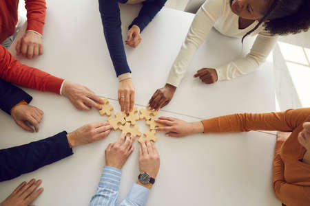 Close up of hands of multiracial office workers assembling wooden puzzles on desk symbolizing development and success. Concept of teamwork, business cooperation and the corporate community Фото со стока