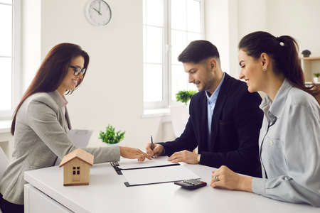 Satisfied millennial couple customer clients signing apartment purchase or rental contract agreement at meeting with broker realtor agent in real estate agency office. Moving home or renting property